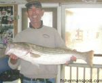David Barr, of Moyock, NC, with an 18 lb. striped bass that bit a sand flea off Outer Banks Pier.