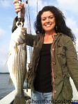 Penny Asby with a tagged striped bass, one of many she hooked on topwater plugs while fishing the Pamlico River with Capt. Mitchell Blake of FishIBX.com.