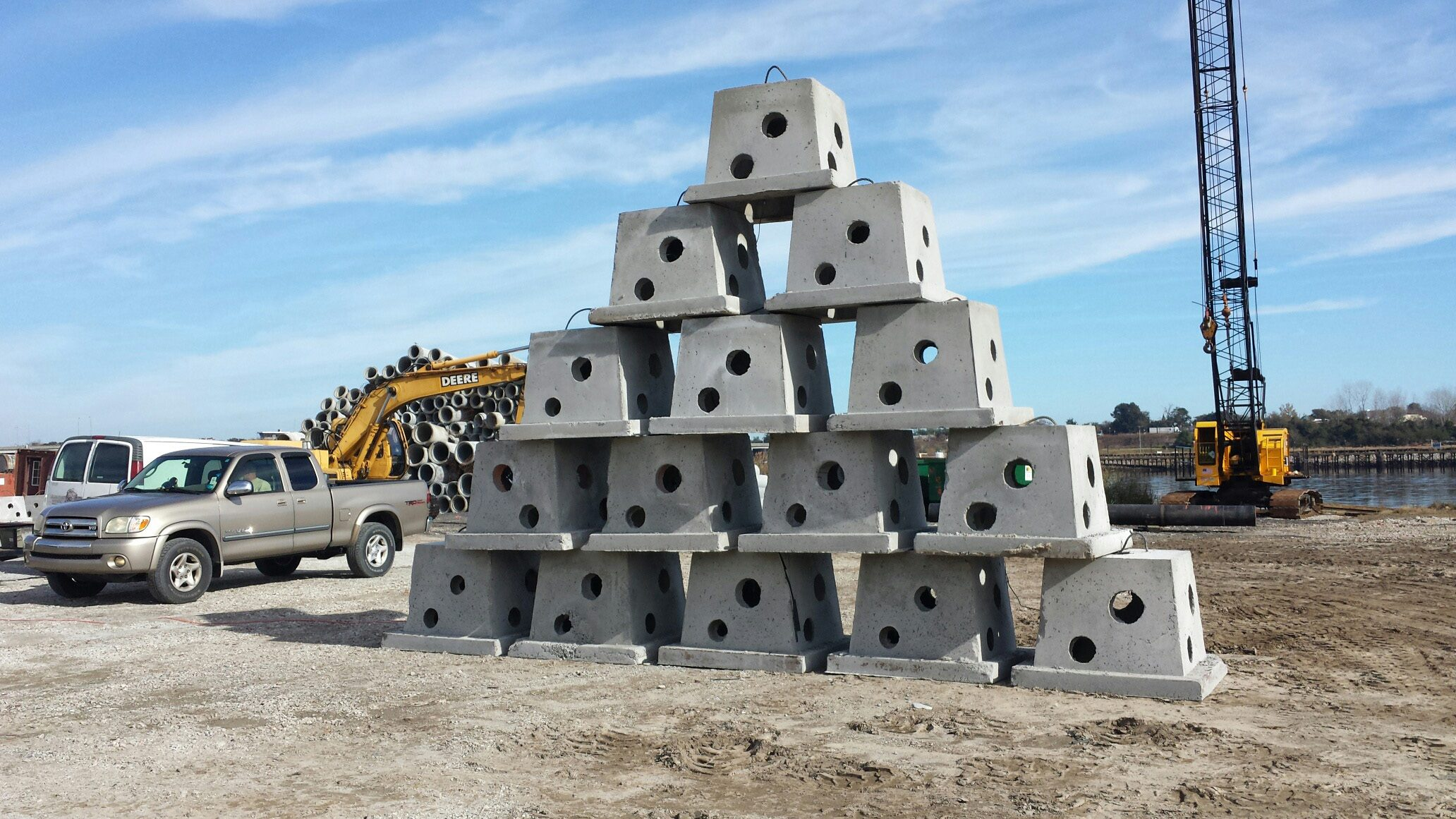 A stack of some of the first Atlantic Pod reef modules awaits deployment alongside some of the scrap concrete pipe acquired by the Onslow Bay Artificial Reef Association.